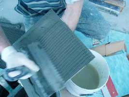 шпателем гребенкой разравниваем клей на обратной стороне плитки